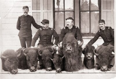 """Men who captured poacher Howell, posed with eight of the confiscated bison heads. In uniform are Dr. Charles M Gandy, Lt John T Nance, Capt George Lawson Scott and Lt Forsythe Hand written on the image """"Poachers Waiting to be Shot"""""""