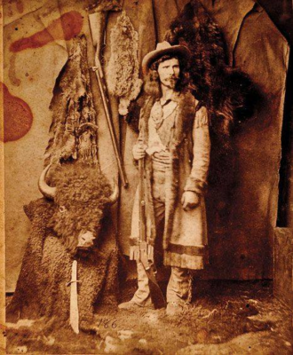 Civilian scout for the 5th Cavalry John Captain Jack Crawford stands surrounded by furs and buffalo by Ben Wittick of Santa Fe, New Mexico.